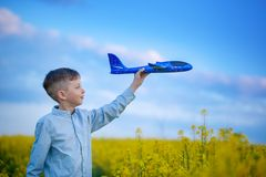 Den gulliga pojken spelar med ett leksakflygplan i den bl?a himlen och dr?mmarna av loppet Hand med den bl?a leksakniv?n arkivbild