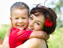 Den gulliga pojken spelar med hans moder utomhus Royaltyfri Bild
