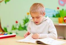 Den gulliga pojken, unge med sakkunniga behöver att se en bok, i rehabiliteringmitt Arkivfoto