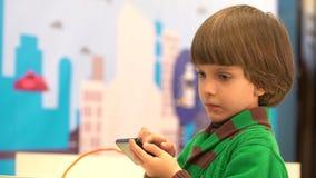 Den gulliga pysen använder en smartphone Roboten visade för barn på den 4th ryska vetenskapsfestivalen Den siktade händelsen stock video