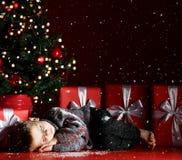 Den gulliga pysen avverkar sovande under julgranen som väntar på Santa Claus Time för mirakel royaltyfri bild