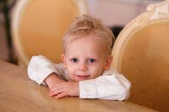 Den gulliga pysen för blont hår sitter på tabellen fotografering för bildbyråer