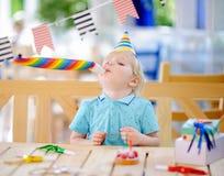 Den gulliga pysen firar födelsedagpartiet med färgrik garnering och bakar ihop Royaltyfri Fotografi