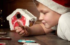 Den gulliga pysen i en julhatt ser pepparkakakuttrandet arkivfoton