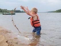 Den gulliga pysen in i den orange flytvästen spelar med sand i floden royaltyfria bilder