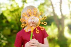 Den gulliga pysen leker med utomhus- stora bubblor Barnet blåser stora och små bubblor samtidigt arkivfoton