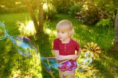 Den gulliga pysen leker med utomhus- stora bubblor Barnet blåser stora och små bubblor samtidigt royaltyfri foto