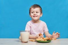 Den gulliga pysen ler och att dricka mjölka och äta kakor royaltyfria bilder