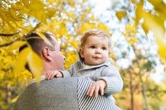 Den gulliga pysen med fadern i höst parkerar Arkivbild