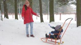 Den gulliga pysen och barnmodern spelar i vintern med insnöat parkera Blå omslag för unge` s och rött på mamman lager videofilmer