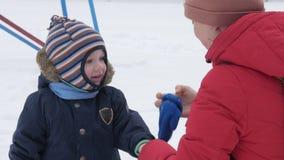 Den gulliga pysen och barnmodern spelar i vintern med insnöat parkera Blå omslag för unge` s och rött på mamman arkivfilmer
