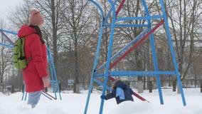 Den gulliga pysen och barnmodern spelar i vintern med insnöat parkera Blå omslag för unge` s och rött på mamman stock video