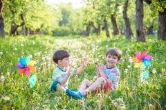 Den gulliga pysen som bevattnar växter med att bevattna kan i trädgården Aktiviteter med barn utomhus fotografering för bildbyråer