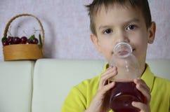 Den gulliga pysen som hemma dricker fruktsaft, körsbärsröd fruktsaft, dricker från en flaska eller ett exponeringsglas med ett su arkivfoto