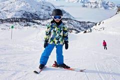 Den gulliga pysen som lär att skida i österrikare, skidar semesterorten Royaltyfri Fotografi