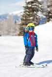 Den gulliga pysen som lyckligt skidar i österrikare, skidar semesterorten i moen Royaltyfria Foton