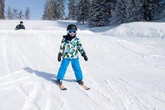 Den gulliga pysen som lyckligt skidar i österrikare, skidar semesterorten i moen Arkivfoto