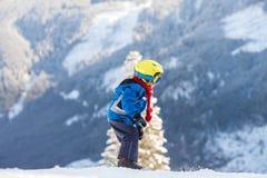 Den gulliga pysen som lyckligt skidar i österrikare, skidar semesterorten i moen Royaltyfri Fotografi