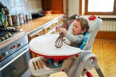 Den gulliga pysen som spelar sammanträde i stol i ett soligt bosatt kök, behandla som ett barn pojken som lyckligt ler royaltyfri fotografi