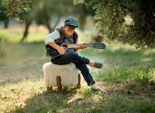Den gulliga pysen spelar gitarren i parkera royaltyfria foton