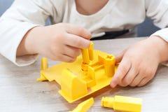 Den gulliga pysen spelar med hjälpmedel Ett litet barn som arbetar med leksakhjälpmedel Royaltyfria Bilder
