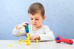 Den gulliga pysen spelar med hjälpmedel Ett litet barn som arbetar med leksakhjälpmedel Royaltyfri Bild