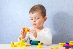 Den gulliga pysen spelar med hjälpmedel Ett litet barn som arbetar med leksakhjälpmedel Arkivfoto