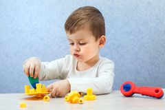 Den gulliga pysen spelar med hjälpmedel Ett litet barn som arbetar med leksakhjälpmedel Arkivbild