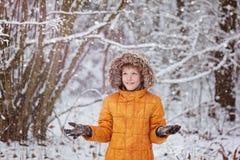 Den gulliga pysen, unge i vinter beklär att gå under den insnöade vintern parkerar Arkivbild
