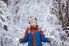 Den gulliga pysen, unge i vinter beklär att gå under den insnöade vintern parkerar Royaltyfri Fotografi