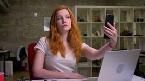 Den gulliga rödhåriga caucasian kvinnlign tar på selfie med den koncentrerade framsidan nära hennes bärbar dator på det skrivbord stock video