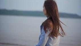 Den gulliga romantiska kvinnan går nära sjön på aftonen stock video