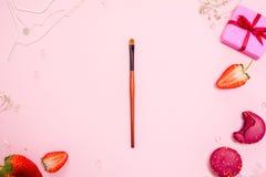 Den gulliga rosa l?genheten l?gger, med en fin makeupborste i mitten glamor?s stil royaltyfri foto
