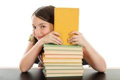 Den gulliga schoolgirlen bak en bunt av bokar Royaltyfri Fotografi