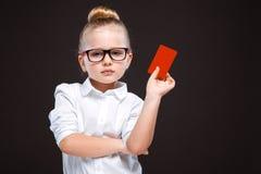 Den gulliga skönhetunga flickan i den vita skjortan och den svarta byxan rymmer det röda kortet Arkivbild