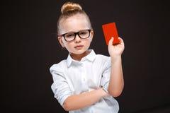 Den gulliga skönhetunga flickan i den vita skjortan och den svarta byxan rymmer det röda kortet Arkivbilder
