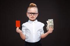 Den gulliga skönhetunga flickan i den vita skjortan och den svarta byxan rymmer det röda kortet och kassa Arkivfoton