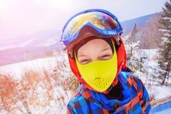 Den gulliga skidåkarepojken i en vinter skidar semesterorten royaltyfria foton