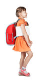 Den gulliga skolflickan går med den röda ryggsäcken på hennes skuldror Royaltyfria Foton