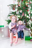 Den gulliga skratta litet barnflickan och hennes små behandla som ett barn brodern under julgranen Royaltyfri Foto