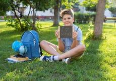 Den gulliga, smarta unga pojken i blå skjorta sitter på gräset bredvid hans skolaryggsäck, jordklotet, den svart tavlan, arbetsbö royaltyfri bild