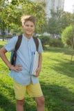 Den gulliga, smarta unga pojken i blåa skjortaställningar med arbetsböcker på gräset i parkerar Utbildning tillbaka till skolan arkivbild