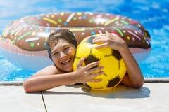 Den gulliga sportiga pojken simmar i pölen med munkcirkeln och har gyckel, leenden, hållapelsiner semester med ungar, ferier, akt royaltyfria bilder