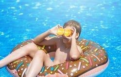Den gulliga sportiga pojken simmar i pölen med munkcirkeln och har gyckel, leenden, hållapelsiner semester med ungar, ferier, akt royaltyfri fotografi