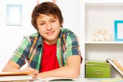 Den gulliga stiliga pojken skriver i lärobok och leende Royaltyfria Foton