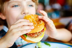 Den gulliga sunda förskole- pojken äter hamburgaresammanträde i kafé utomhus Arkivfoto