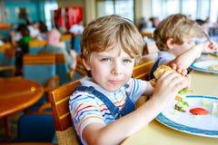 Den gulliga sunda förskole- pojken äter hamburgaresammanträde i skolakantin Arkivfoto