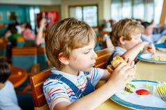Den gulliga sunda förskole- ungepojken äter hamburgaresammanträde i skola- eller barnkammarekafé Lyckligt barn som äter sunt orga arkivfoto