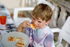 Den gulliga sunda förskole- ungepojken äter nytt pizzasammanträde på terrass i sommar, utomhus Royaltyfri Foto