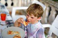 Den gulliga sunda förskole- ungepojken äter nytt pizzasammanträde på terrass i sommar, utomhus Royaltyfria Bilder